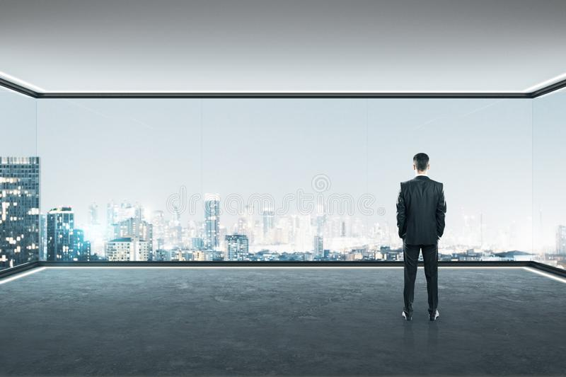 Businessman in modern office. Businessman looking out of window in modern empty spacious office interior with illuminated panoramic city view. Research concept stock photos