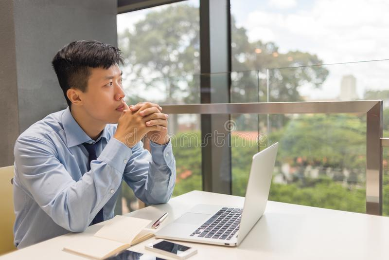 Businessman looking outside the office and thinking stock photography