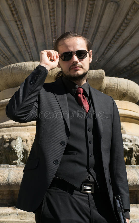 Businessman looking at the photographer and adjusting his sun glasses stock image