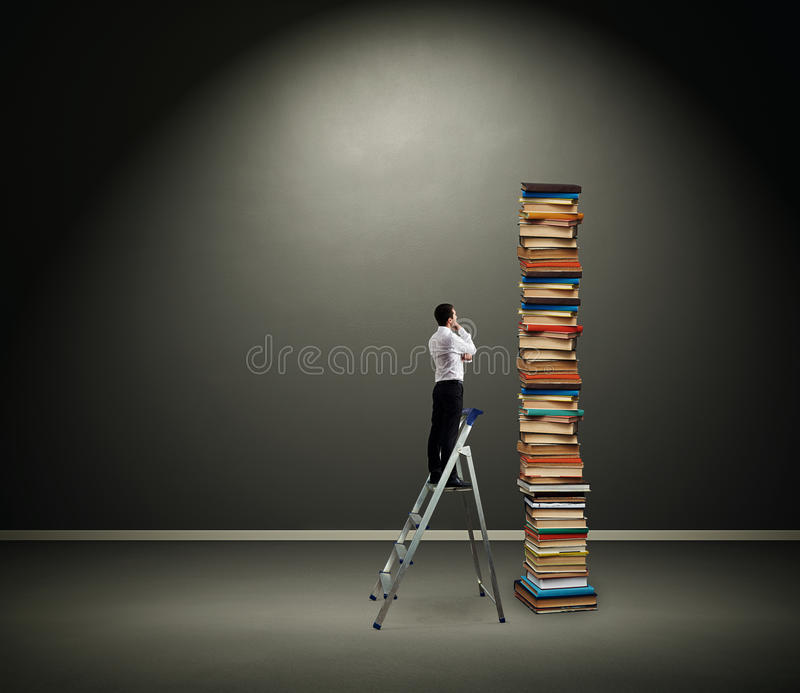 Businessman Looking At Pile Of Books Royalty Free Stock Photo