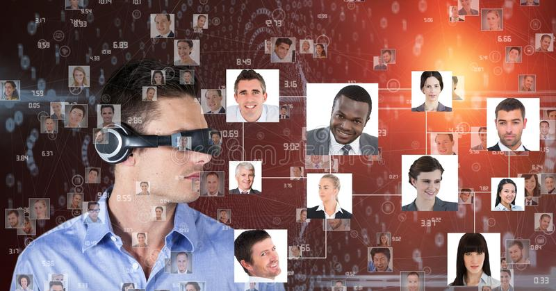 Businessman looking at portraits through VR headphones stock images