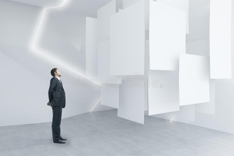 Businessman looking at posters. Businessman looking at empty posters in abstract exhibition room. Mock up, 3D Rendering stock photo