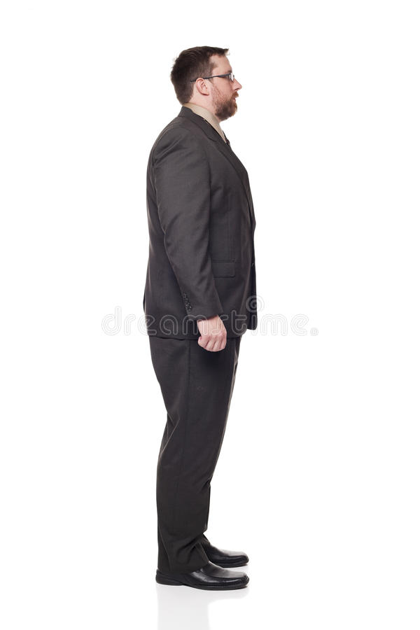 Businessman looking right full length. Isolated full length studio shot of the side view of a businessman in full suit looking away from the camera to the right royalty free stock photos