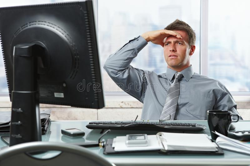 Businessman looking at screen in office stock image
