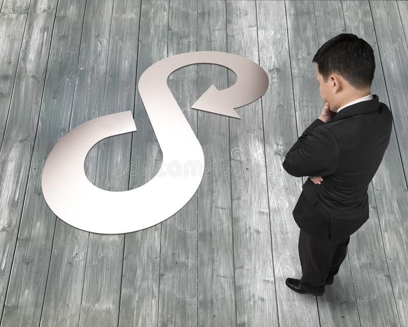 Businessman looking at sheet metal in arrow infinity recycling symbol. Circular economy concept. Thinking businessman looking at silver sheet metal in arrow stock photo