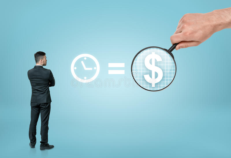 Businessman looking at sigh 'time is money' with big man's hand enlarging dollar sign by magnifier royalty free stock images