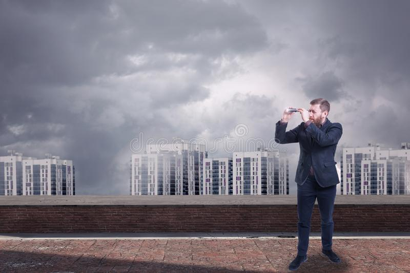 A businessman looking with spyglass for best deal. A businessman looking with a spyglass against a city downtown with stormy gray sky stock photos