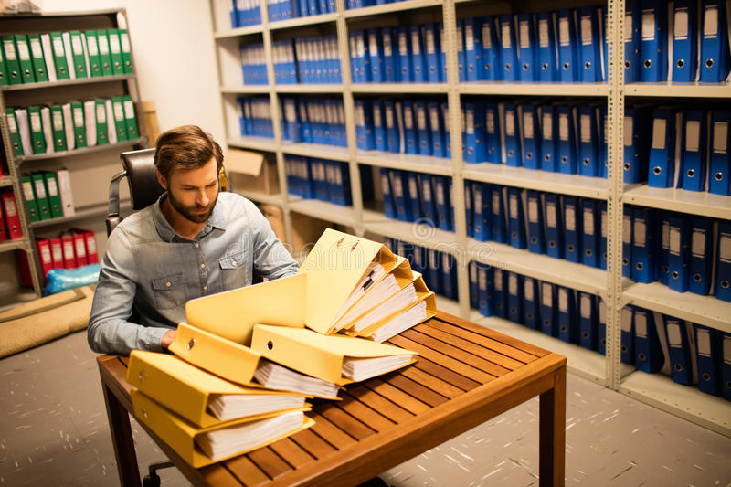 Businessman looking at stack of files on table in storage room stock photo