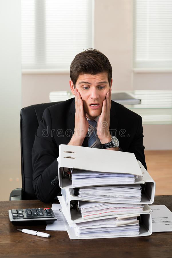 Businessman Looking At Stack Of Folders stock photo