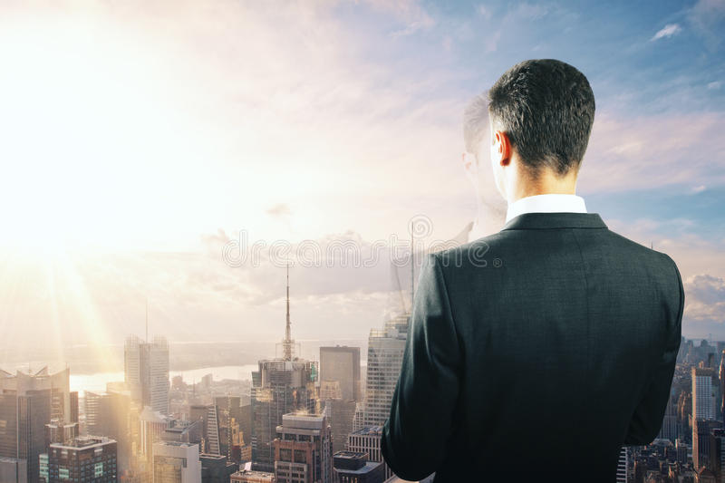 Businessman looking at sunrise from the top of building stock image