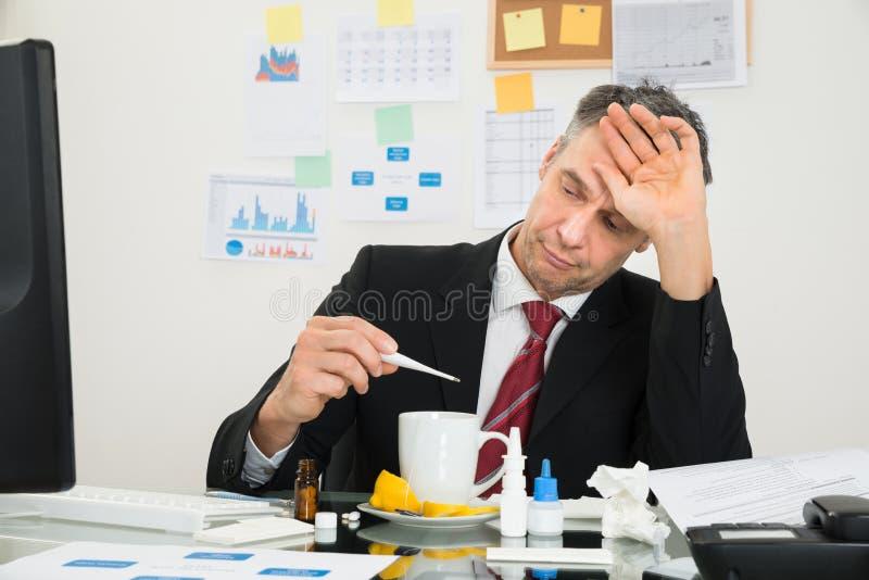Businessman looking at thermometer. Sick Mature Businessman Suffering From Fever Looking At Thermometer stock photos