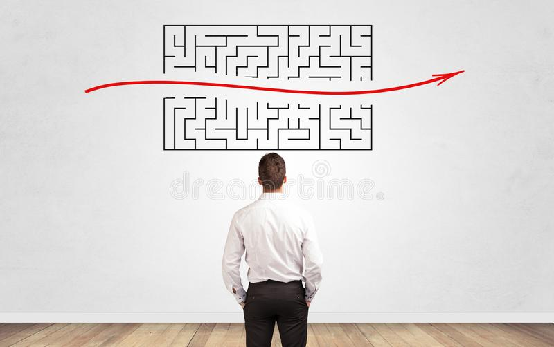 Businessman looking to a maze on a wall royalty free stock photos
