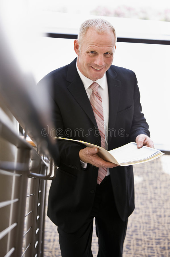 Businessman looking up from paperwork on stairs royalty free stock image