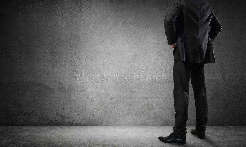 Businessman looking at wall. Back view of confident businessman in empty concrete room stock photography