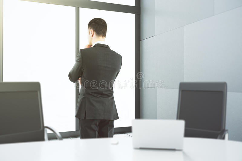 Businessman looking through a window in the meeting room stock image