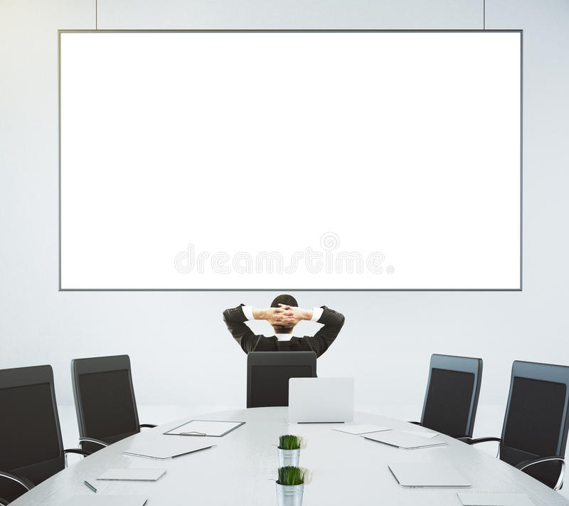 Businessman looks at blank poster on the wall in modern conference room, mock up stock photo