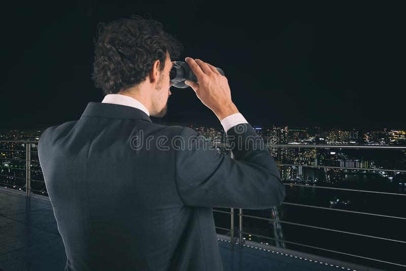 Businessman looks at the city with binoculars during night. Future and new business opportunity concept royalty free stock photography