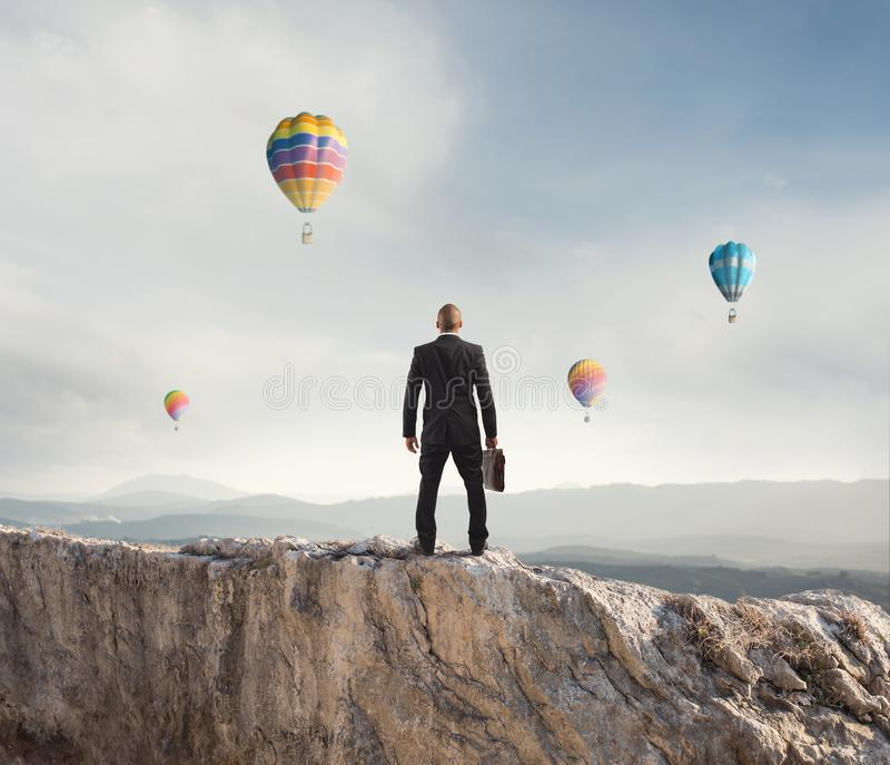 Businessman looks far to the future of the business. On mountain stock photography