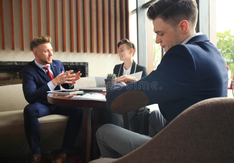 Businessman looks at his wrist watch checking the time. Businessperson sitting a meeting and working at background. Businessman looks at his wrist watch royalty free stock photo