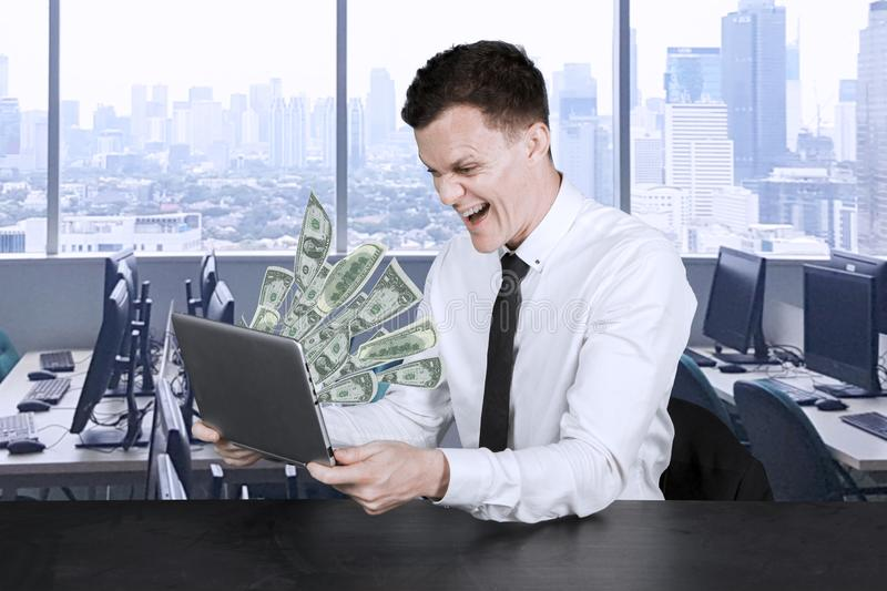 Businessman looks at money out of his laptop royalty free stock photo