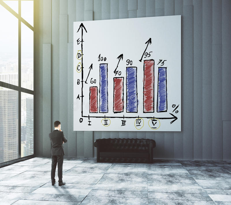 Businessman looks at the poster with business graph in modern room with leather sofa and big windows stock photography