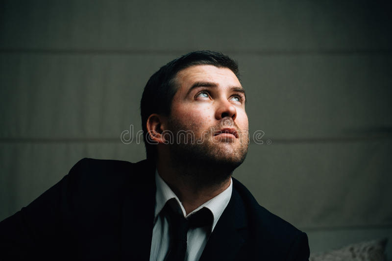 Businessman looks up the light. Young businessman looks up the light in a dark room stock image