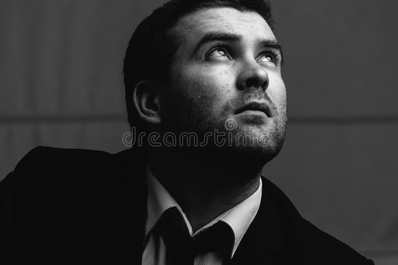 Businessman looks up the light. Young businessman looks up the light in a dark room. Black and white photography stock photos