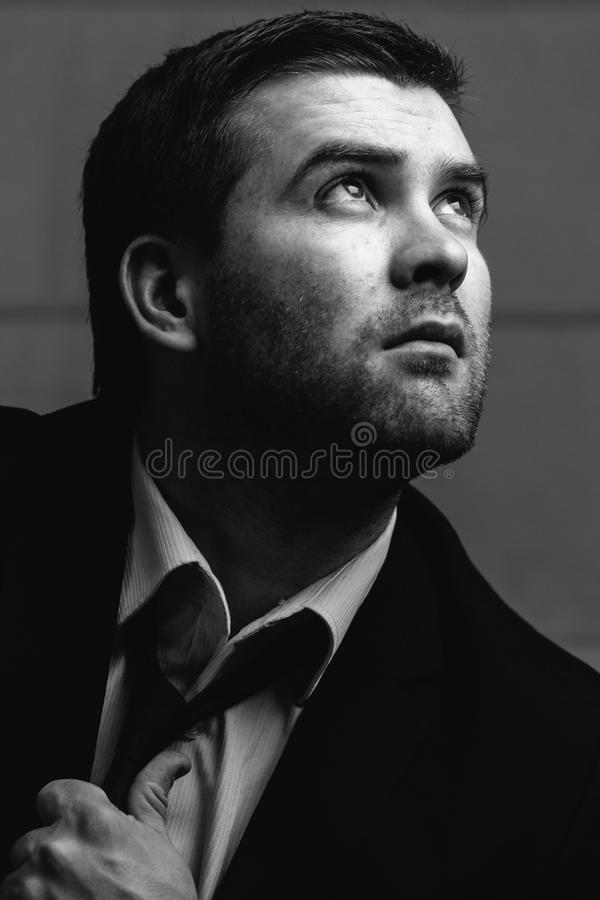 Businessman looks up the light. Young businessman looks up the light in a dark room. Black and white photography stock images