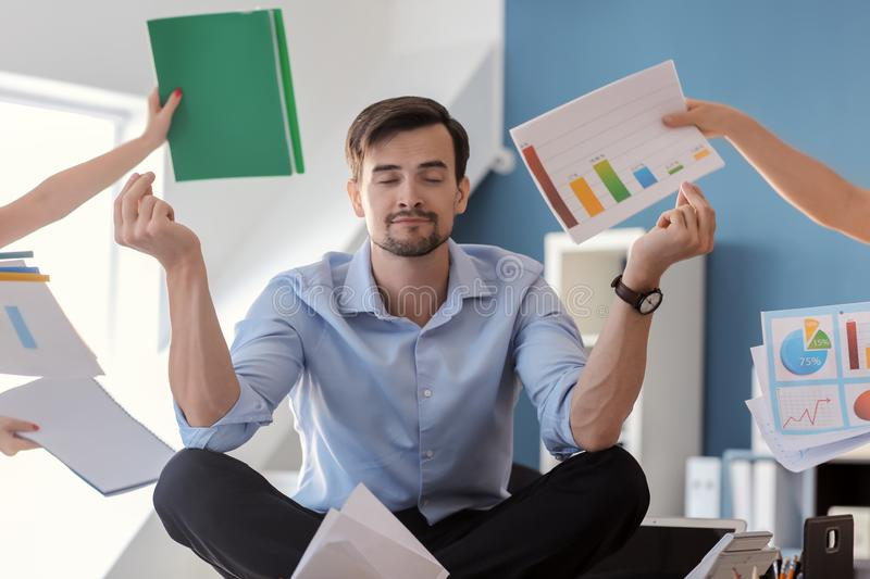Businessman with a lot of work to do meditating in office royalty free stock photos