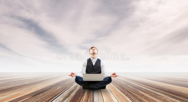 Businessman in lotus pose. Mixed media stock photo