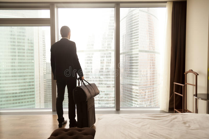 Businessman with luggage ready for business trip. Man in business suit standing with suitcase and handbag in luxury hotel room, looking on modern cityscape royalty free stock photo