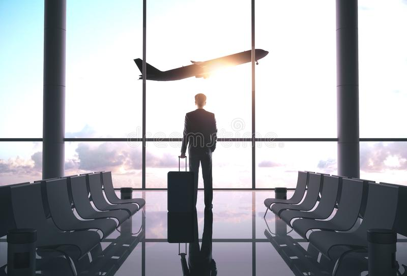 Businessman standing in airport. Businessman  with luggage standing in airport and looking at airplane flying in sky. Travel and transportation concept royalty free stock images