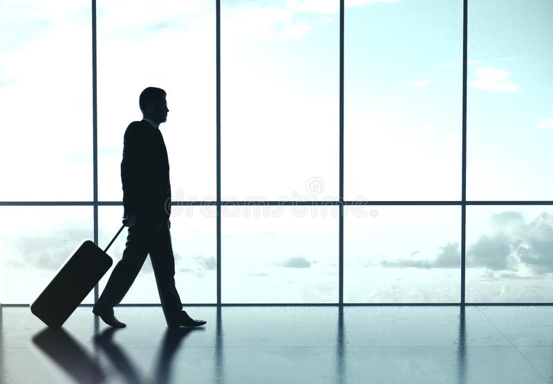 Businessman walking at airport. Businessman with luggage is walking at the airport. Travel and transportation concept stock photos