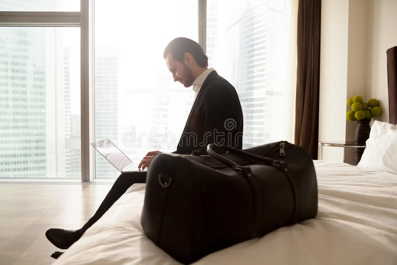 Businessman with luggage works on laptop at hotel. Business tourist communicates online with colleagues from hotel. Businessman with luggage working on laptop royalty free stock images