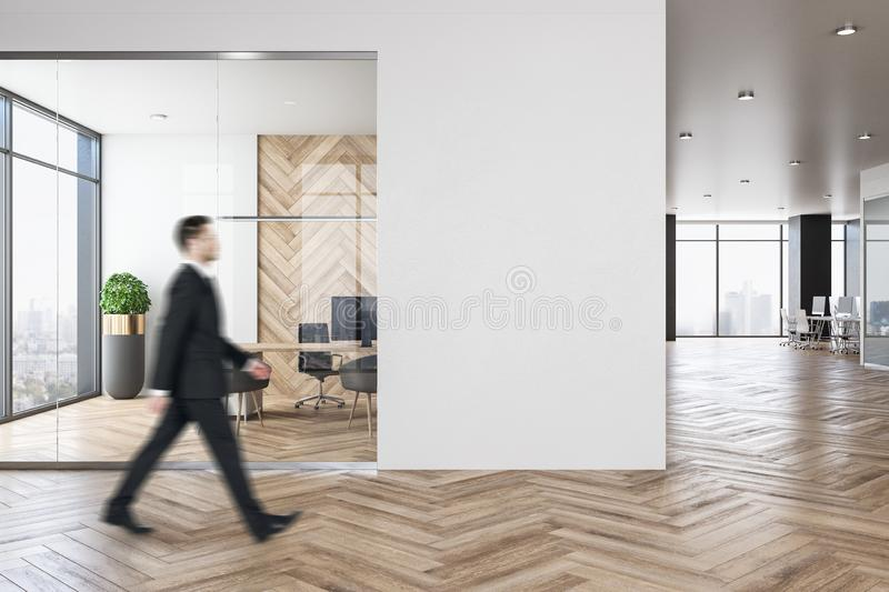 Businessman in luxury office with copyspace. Side view of businessman walking in luxury blurry office room interior with city view, empty copyspace and daylight royalty free stock photos