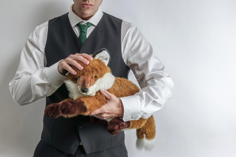 Businessman / mafia boss in suit vest holding a stuffed fox. stock photography