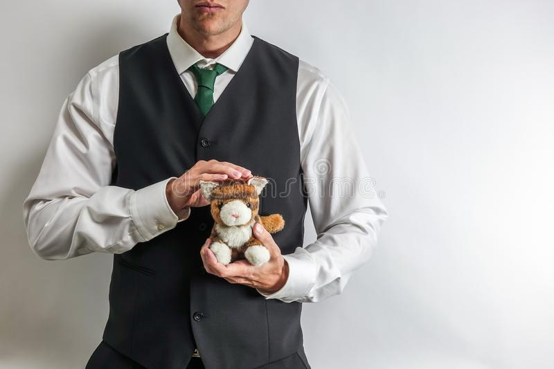 Businessman / mafia boss in suit vest holding a stuffed toy cat. stock image