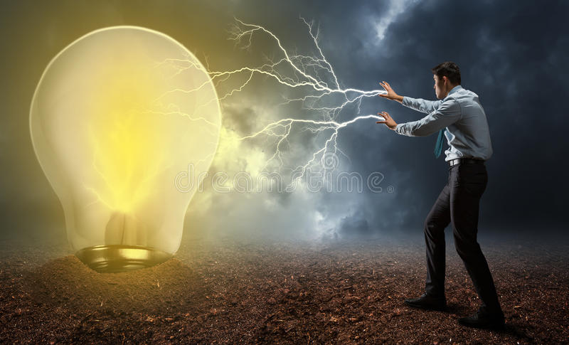 Businessman with magic. Businessman with lightnings from his palms turning on the lamp stock images
