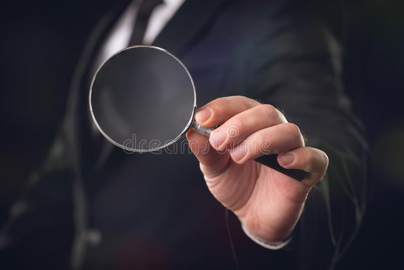 Businessman with Magnifying Glass on Dark royalty free illustration