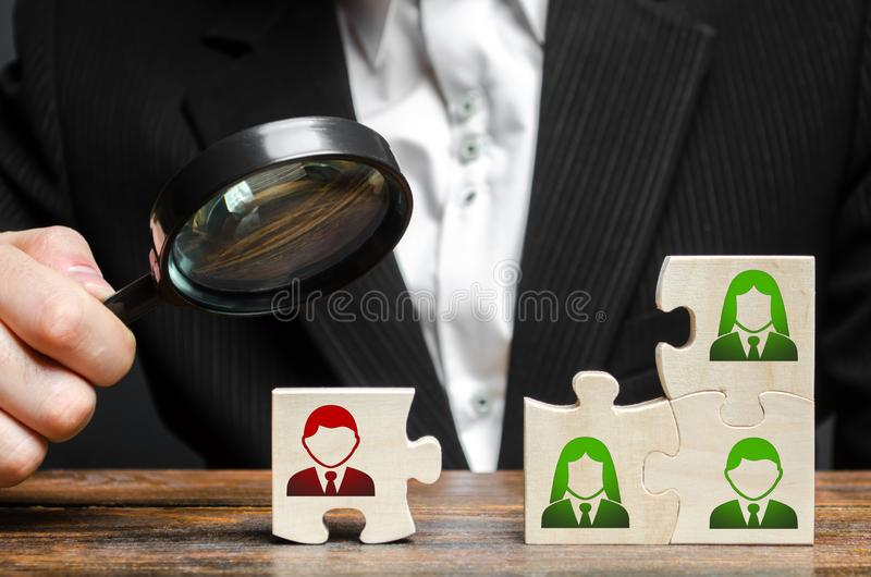 Businessman with a magnifying glass examines puzzle with an incompetent and toxic worker. The concept of the organization stock image