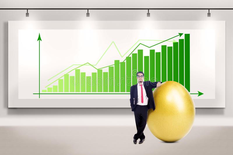 Businessman makes big profit. Businessman is standing beside a big golden egg on profit bar chart background royalty free stock images