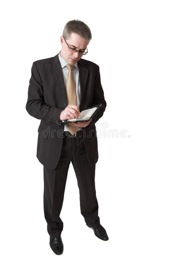 Businessman makes entry in notebook