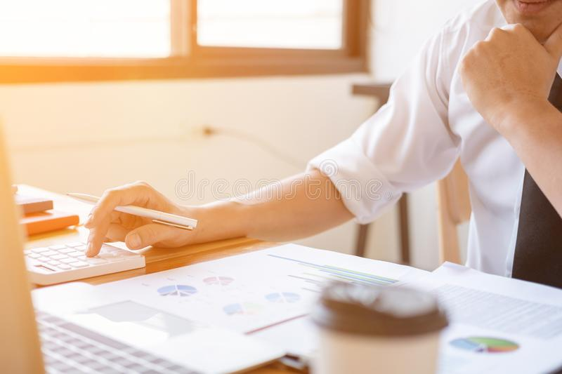 Businessman making calculation with pen in hand, finances concept royalty free stock images