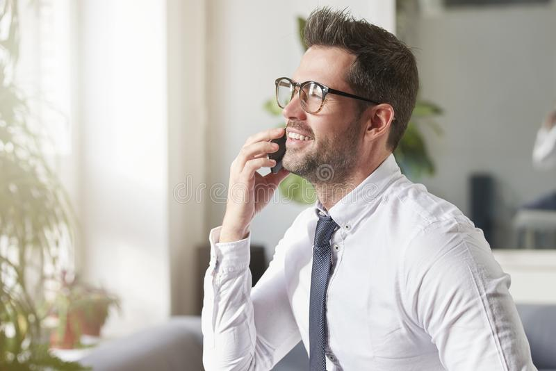 Businessman making a call while sitting in the office stock photos
