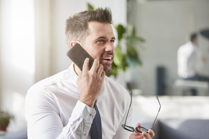 Businessman making a call while sitting in the office stock photography