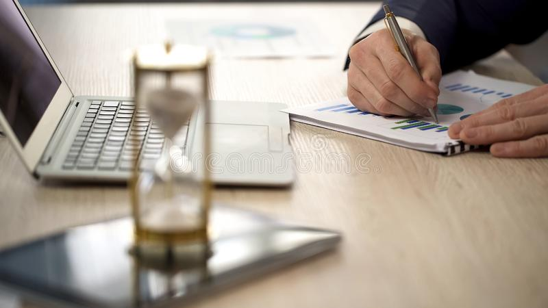 Businessman making marks on graph, sandglass standing on office desk, time. Stock photo royalty free stock images
