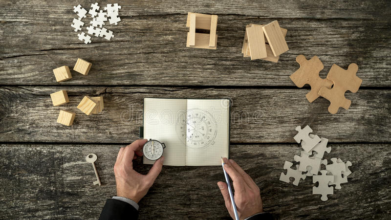 Businessman making plan and business strategy decisions as he sk. Etches a compass he is holding into his notebook. Various cubes, pegs, puzzles and a key lying stock image
