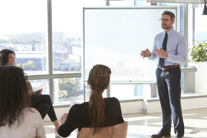 Businessman Making Presentation To Colleagues In Office stock photography