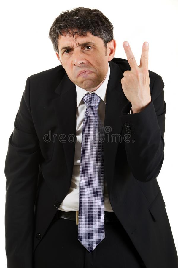 Businessman making a rude v-sign. Businessman making a rude derogatory v-sign gesture with his hand while grimacing and frowning at the camera, three quarter stock photo