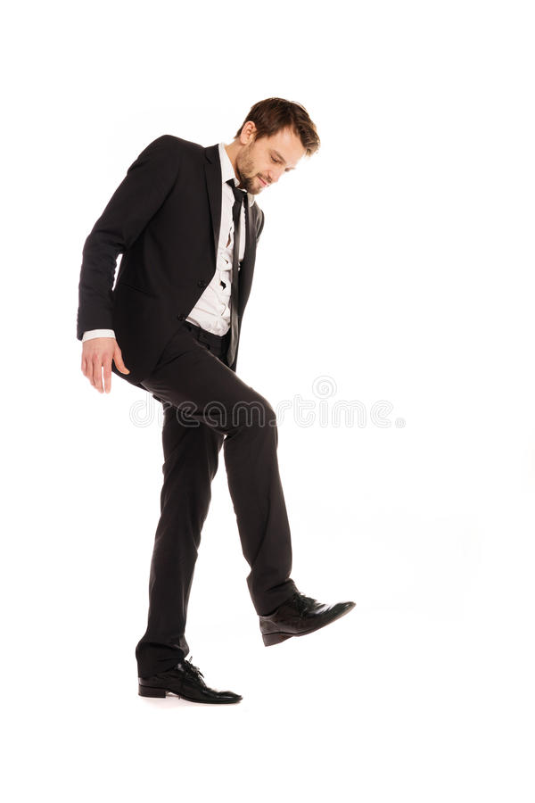 Businessman making a stamping gesture. Handsome young businessman in a suit making a stamping gesture with his foot raising it in the air, isolated on white royalty free stock image